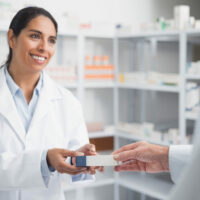 Smiling pharmacist supports patient
